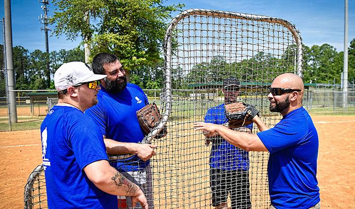 Hombres con camisas azules preparando el equipo de béisbol