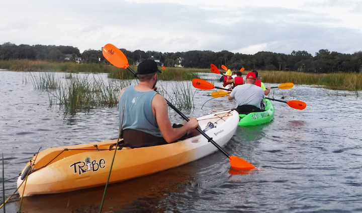 A line of men kayaking in what looks like a swamp